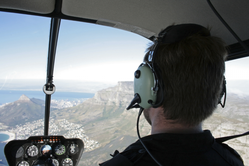 Image of a pilot in a helicopter flying over Table Mountain